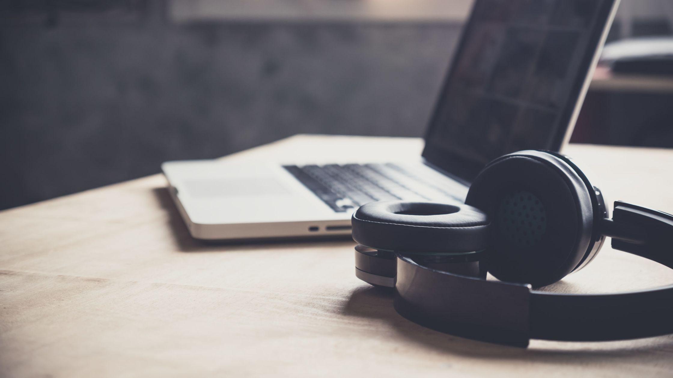 Auf einem Schreibtisch liegen Laptop und Kopfhörer