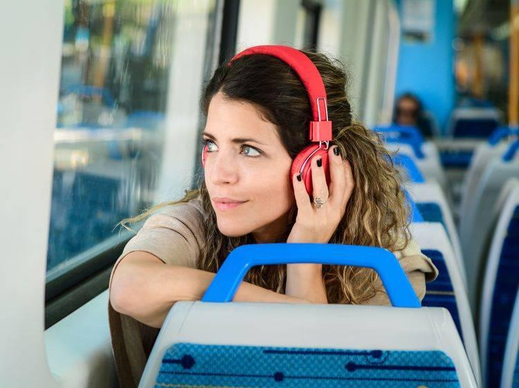 Frau mit Kopfhörern in der Bahn