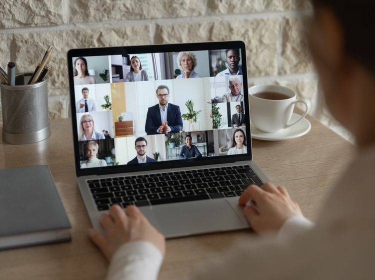Mann hat den Laptop geöffnet und nimmt an einer Videokonferenz teil
