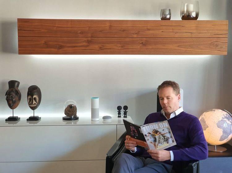 Mann sitzt im Wohnzimmer neben einem Sprachassistenten und liest eine Zeitschrift