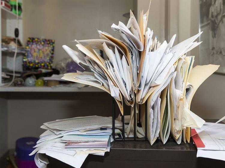 Unordentlicher Arbeitsplatz mit vielen unsortierten Dokumenten