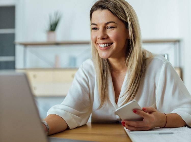 Lächelnde, junge Frau sitzt am Laptop mit Smartphone in der Hand