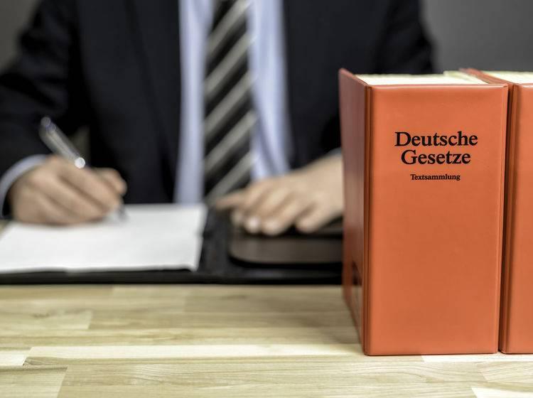 Anwalt sitzt am Schreibtisch. Im Vordergrund ein Gesetzbuch.