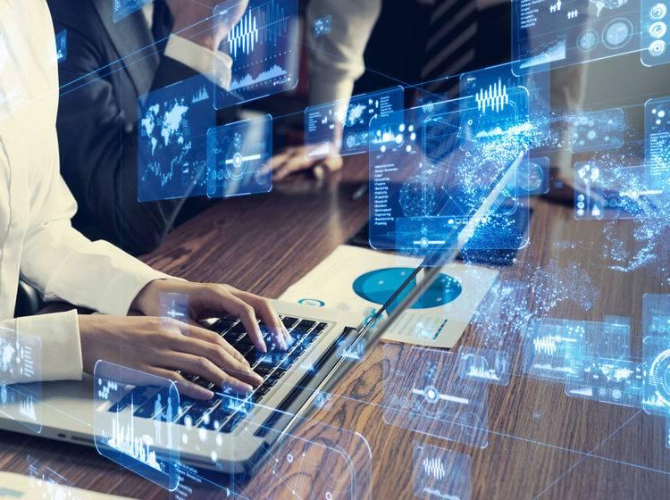 KI im Content Marketing bei Content Fleet. Kollegen sitzen vor einem Laptop und schauen auf die Künstliche Intelligenz.